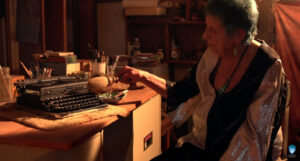 ruth weiss at home with typewriter by Melody C. Miller