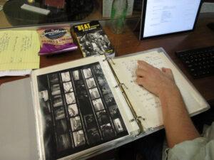 Volunteer David Zeeman cross-referencing C.R. Snyder's handwritten notes with a contact sheet