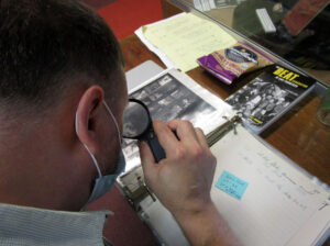 Volunteer David Zeeman poring carefully over the contact sheets, identifying people and places